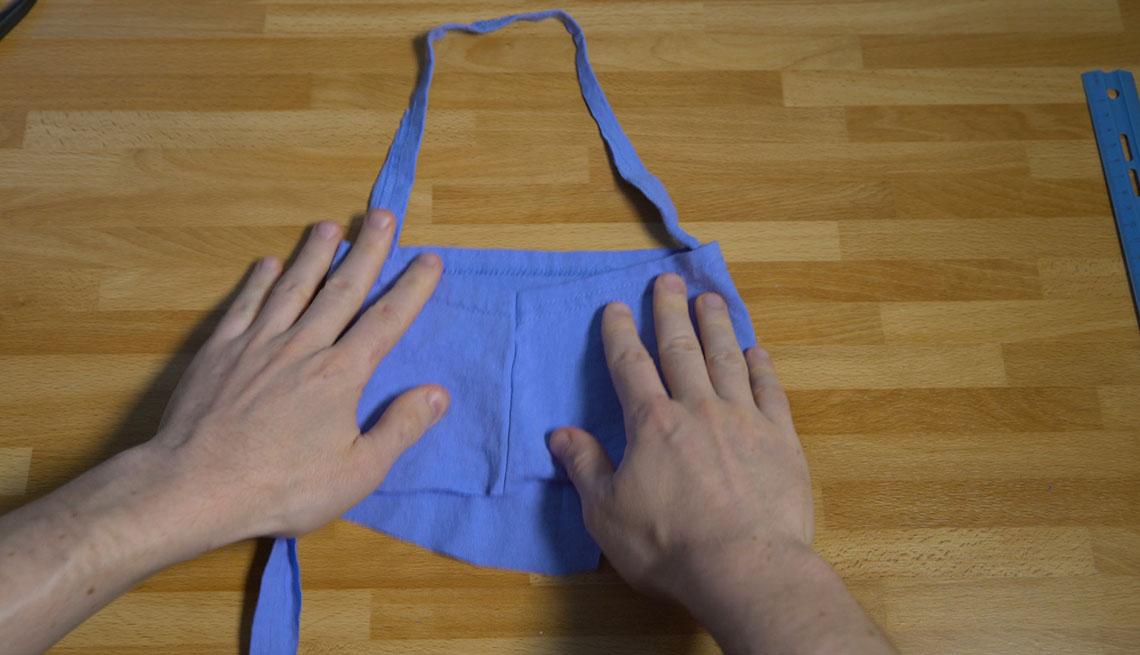 Una persona hace una mascarilla con pedazos de una camisa