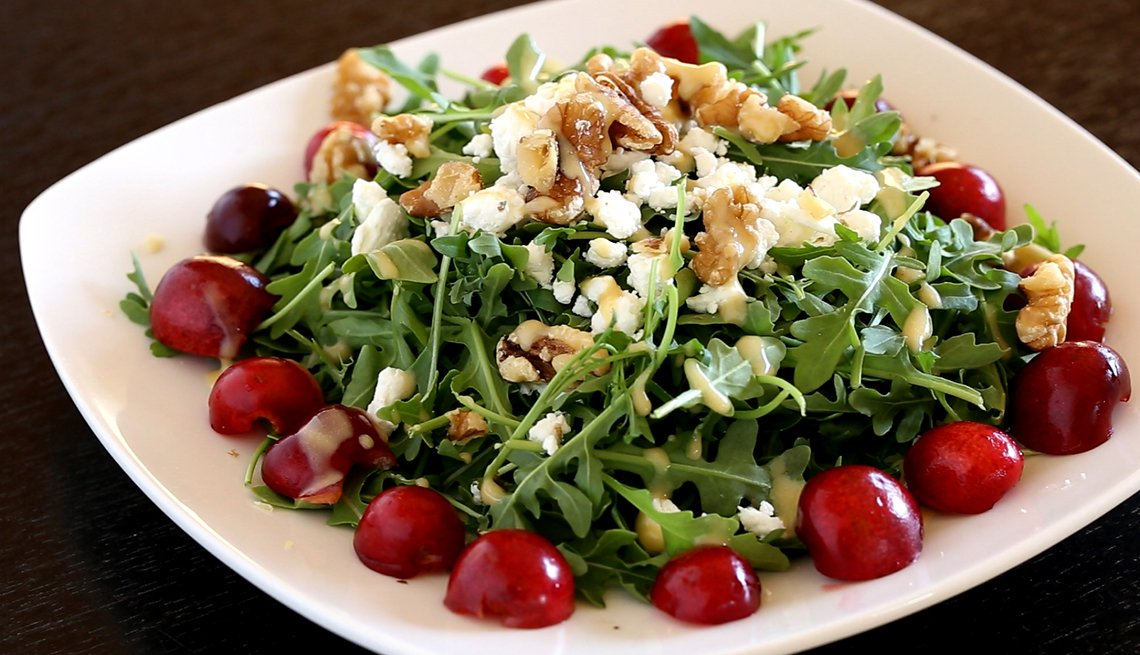 plate of arugula lettuce salad with sliced cherries goat cheese and nuts