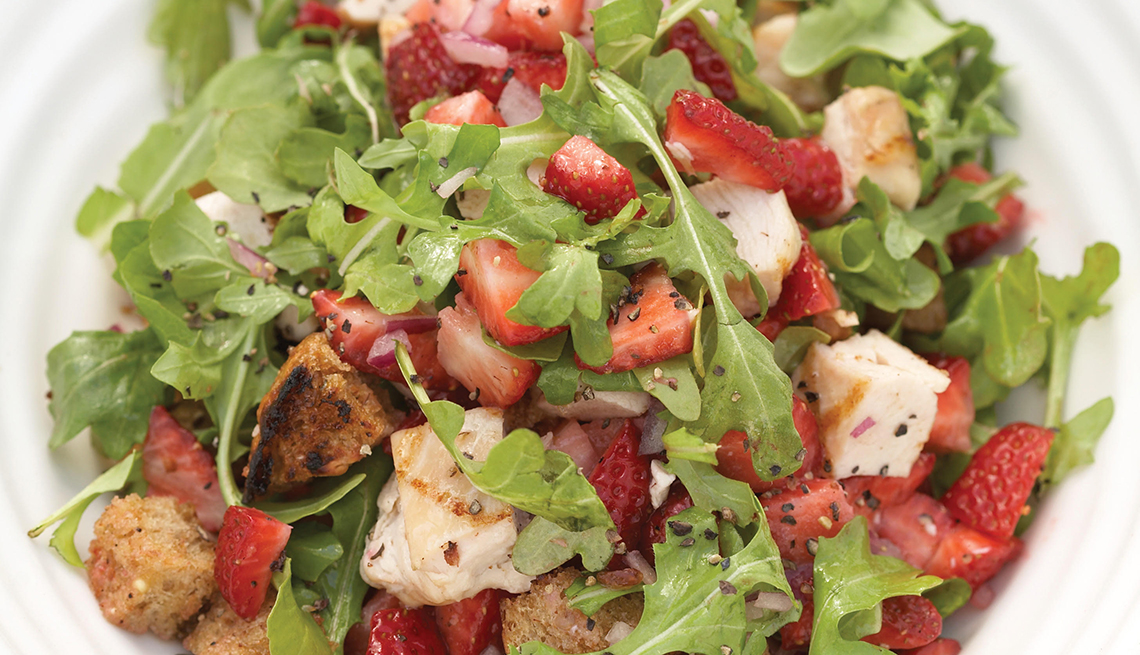 close up of a plate full of arugula salad with strawberries and chicken