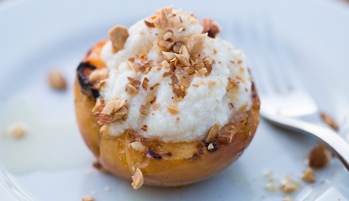 plate containing a grilled peach filled with ricotta cream and topped with nuts
