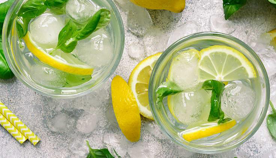 two glasses of summery looking lemonade with herb leaves and lemon slices overhead shot