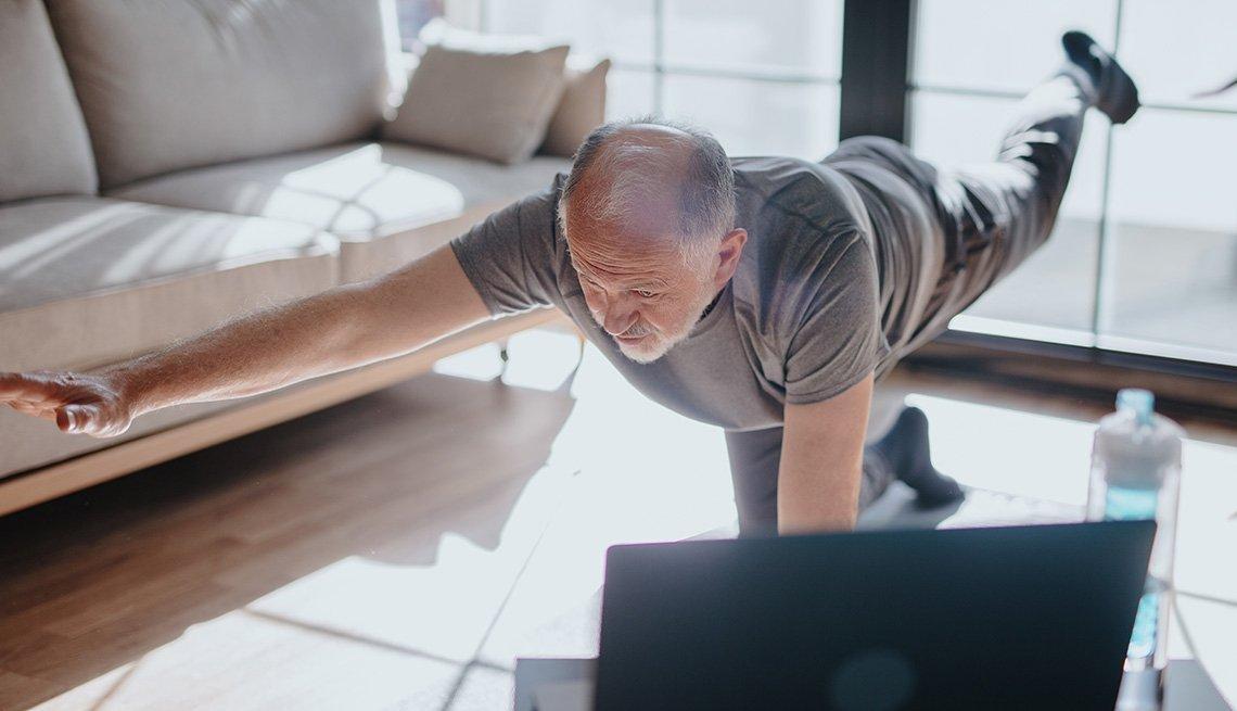 Un hombre hace ejercicios en la sala de su casa