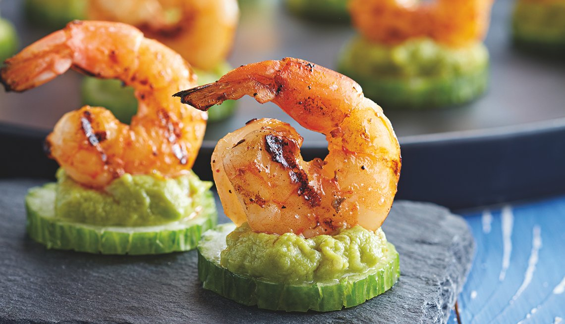 appetizers of grilled shrimp atop a cucumber slice and guacamole