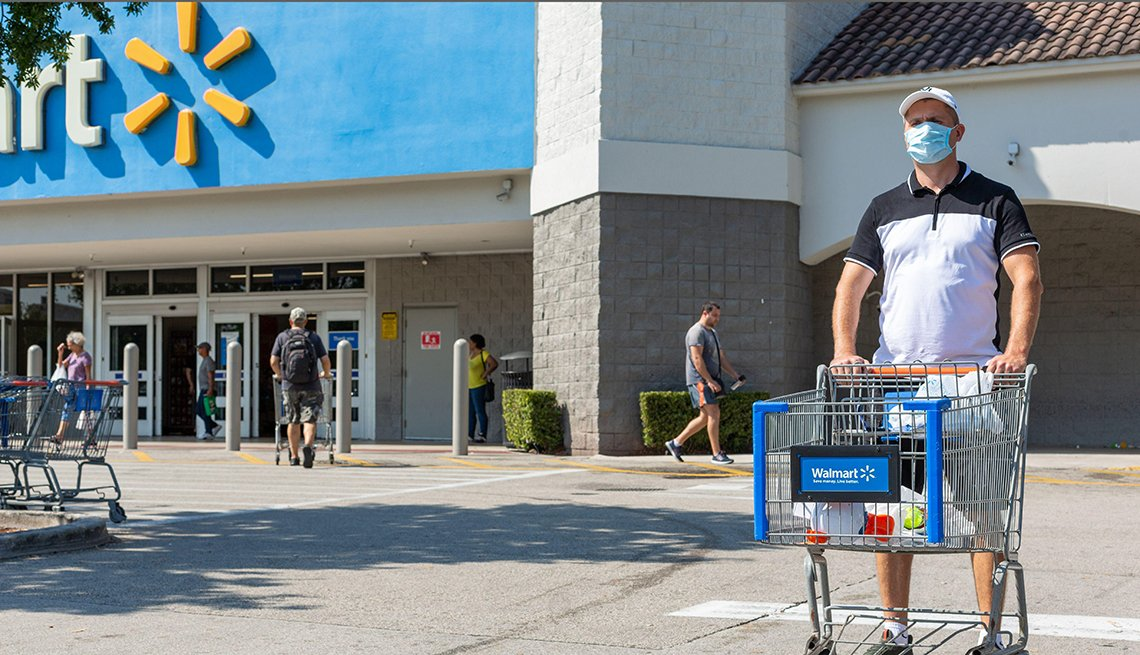 a shopper pushing a shopping cart outside a walmart store
