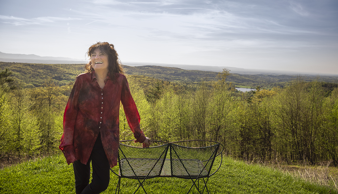 ruth reichl stands on a hilltop overlooking mountains and a river in her yard