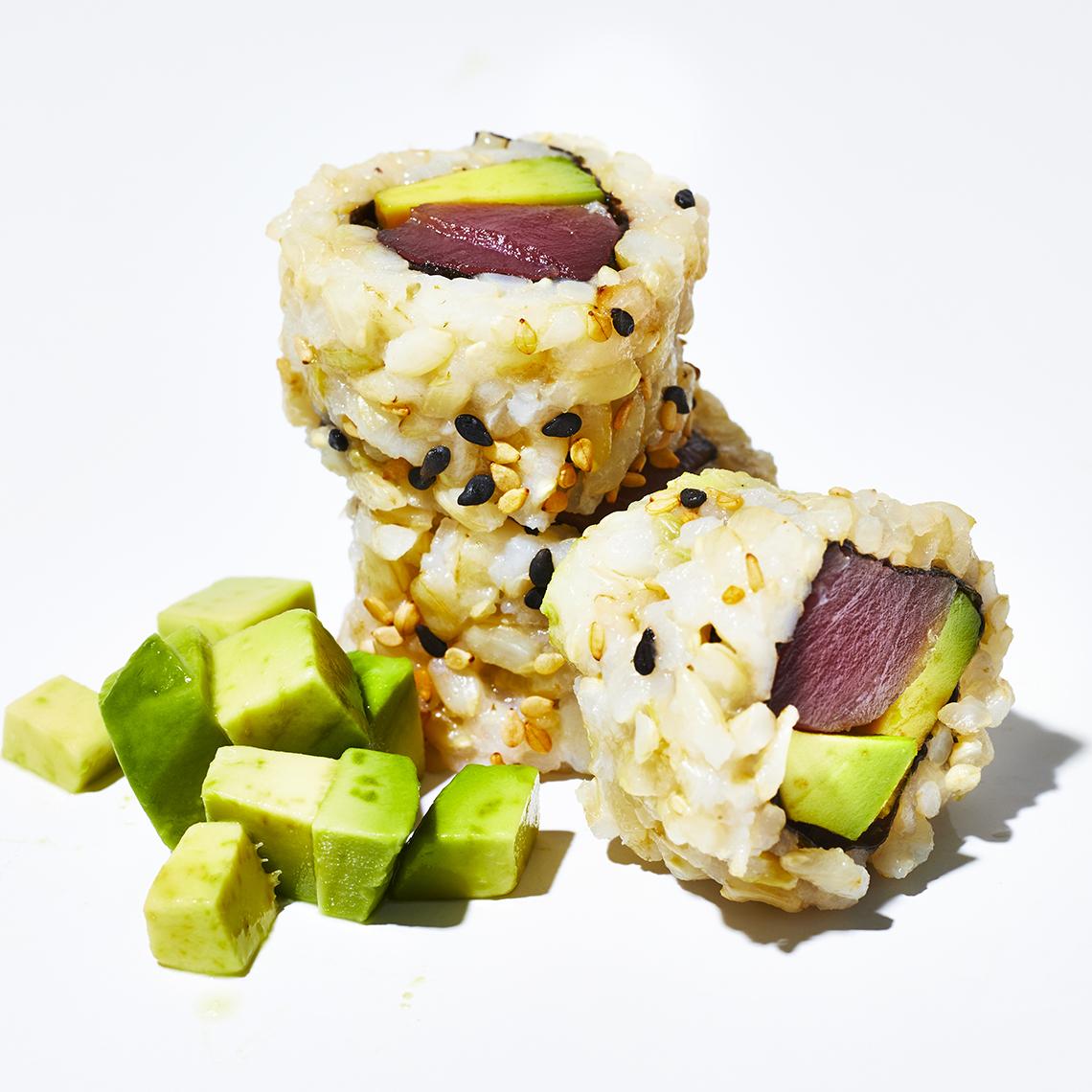 Rodajas de sushi roll de atún con arroz integral y aguacate