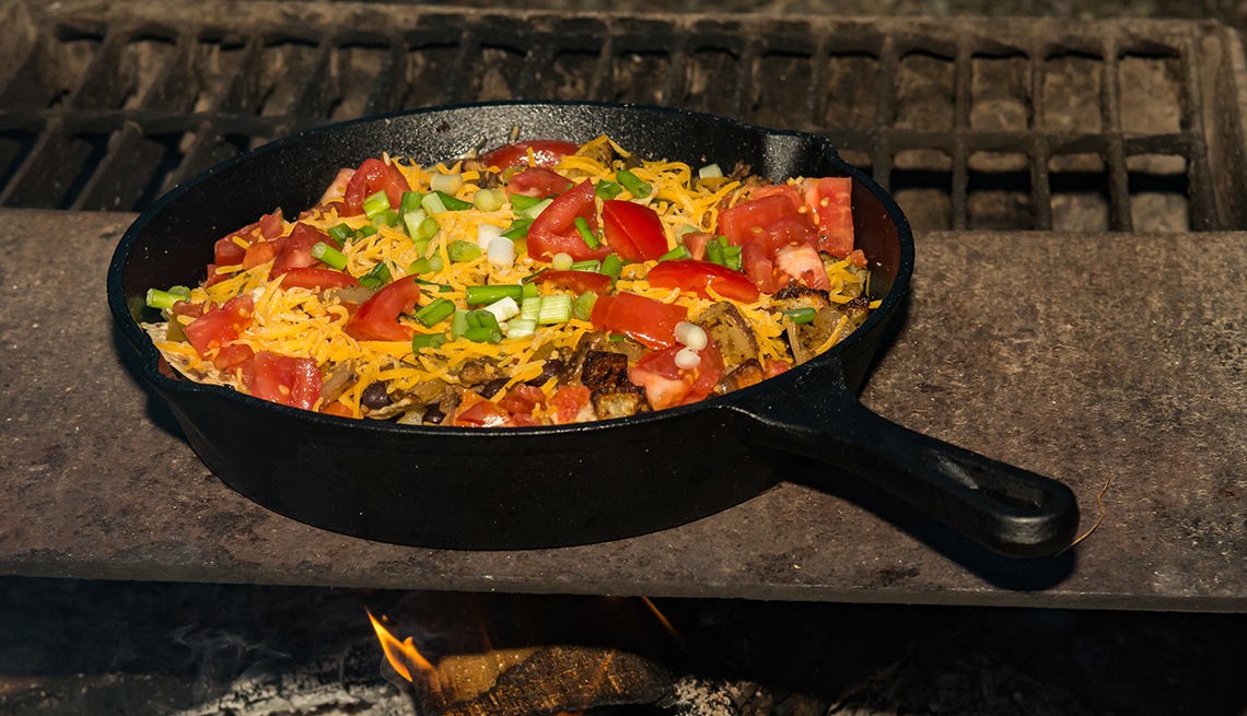 A cast iron skillet filled with nacho toppings placed over a campfire