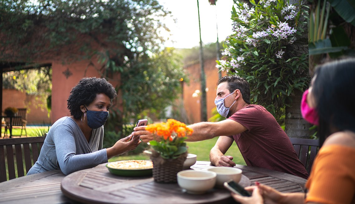 Friends reunited in the backyard, talking and using smartphone while wearing face masks