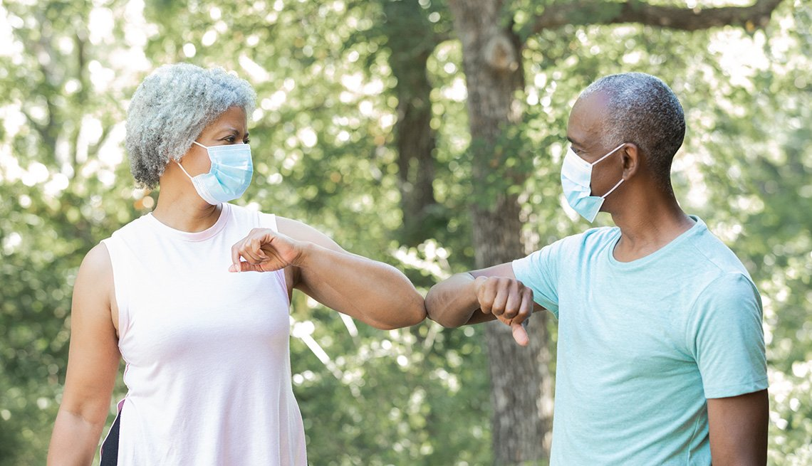 Man and woman wearing masks greet each other by touching elbows