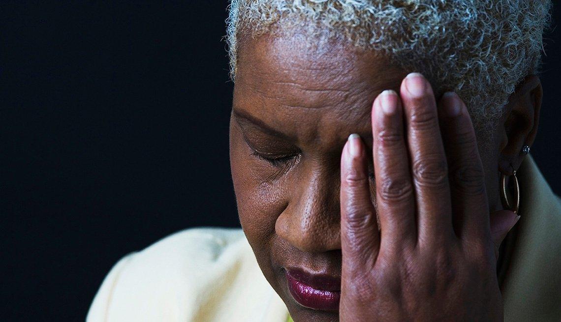 Una mujer con su mano en la cara en señal de dolor