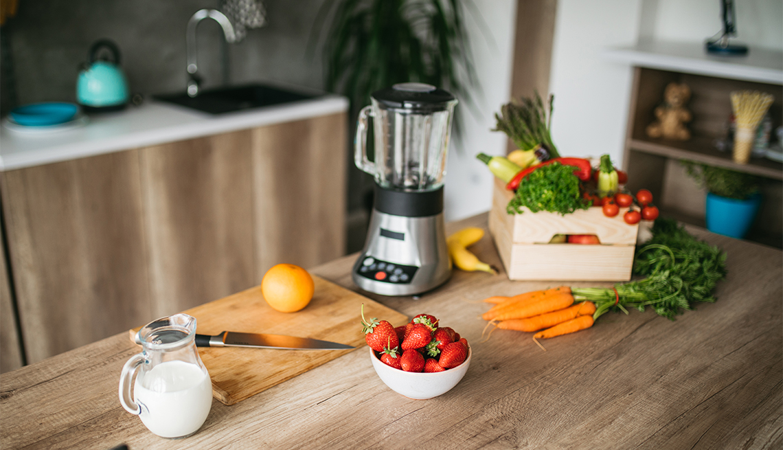 Healthy food for a smoothie on a counter near a blender