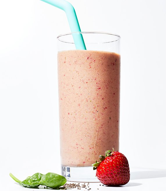 smoothie in tall glass with strawberry and greens
