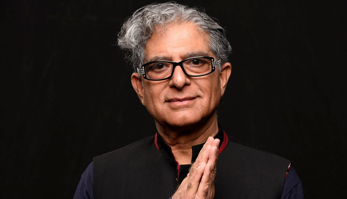 deepak chopra looking at the camera holding up his hands with the palms pressed together