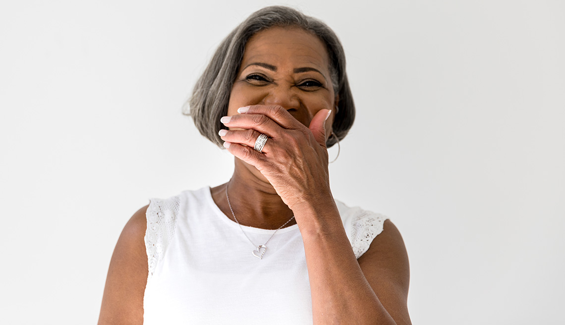 Woman covering her mouth and laughing