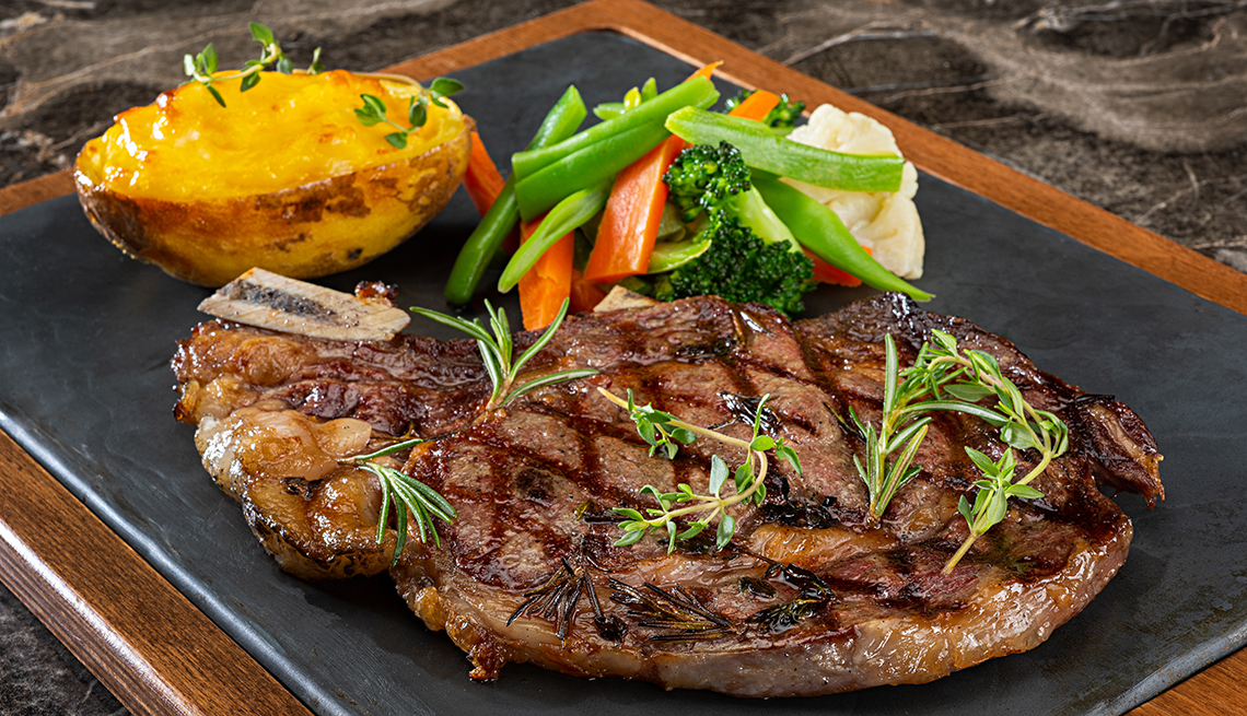 Close up of steak, vegetables and a baked potato on a platter.