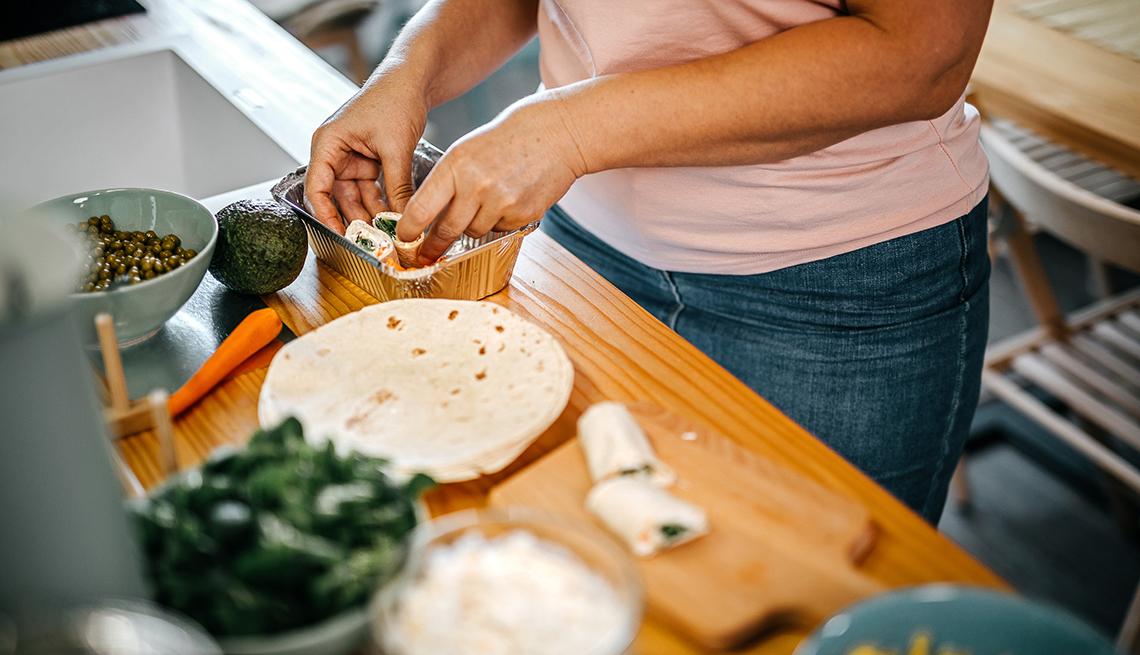 Una mujer preparando en la cocina una comida con vegetales.