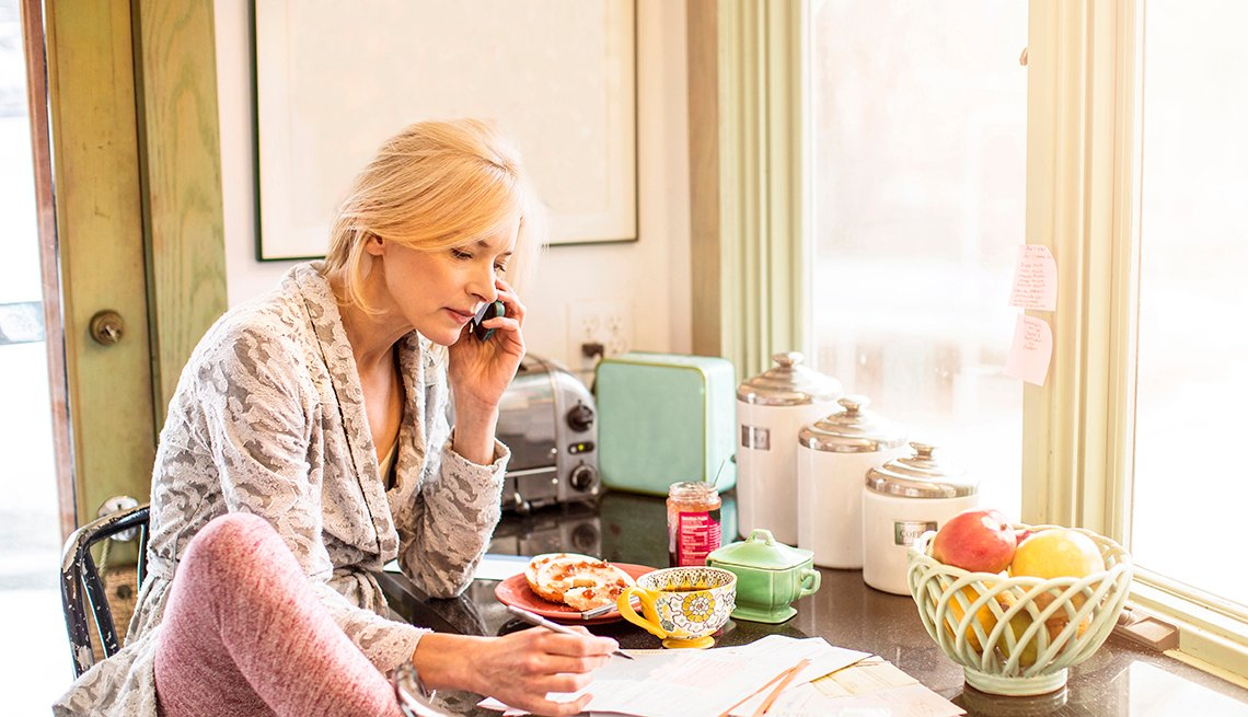 Una mujer en su cocina paga sus facturas por teléfono
