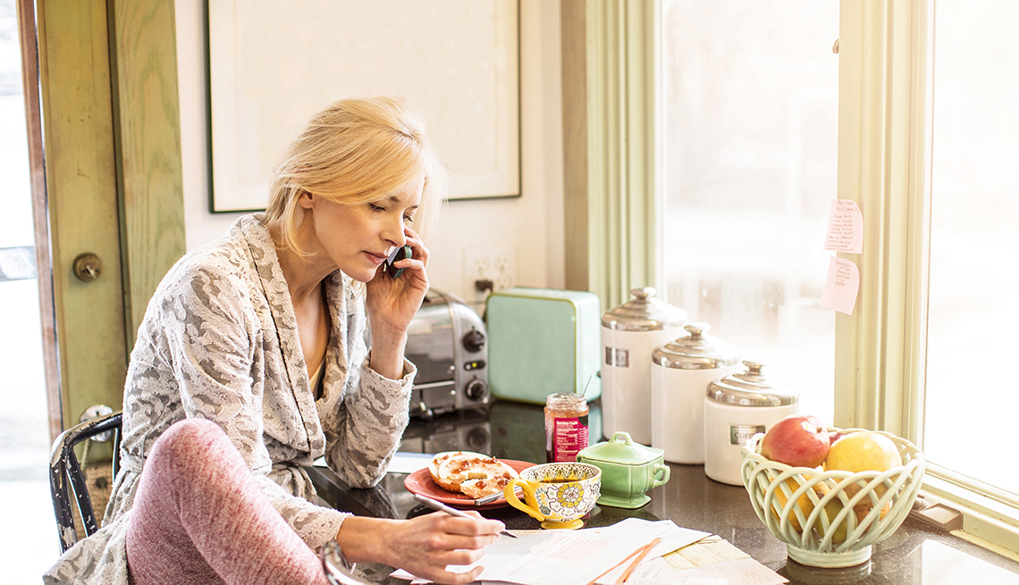 Woman paying her bills, talking on the phone and eating