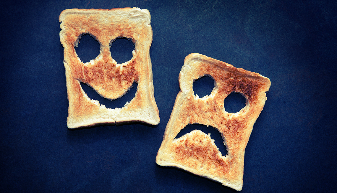 Two slices of toasted bread with happy and unhappy faces cut out