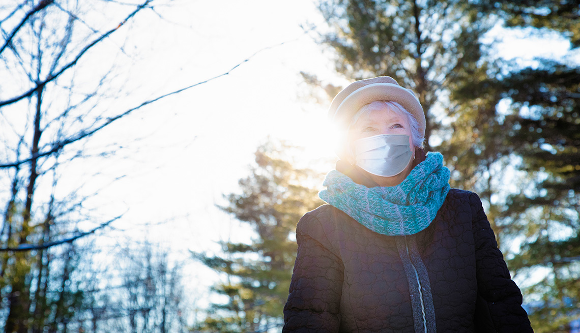Woman wearing a face mask taking a walk in the winter
