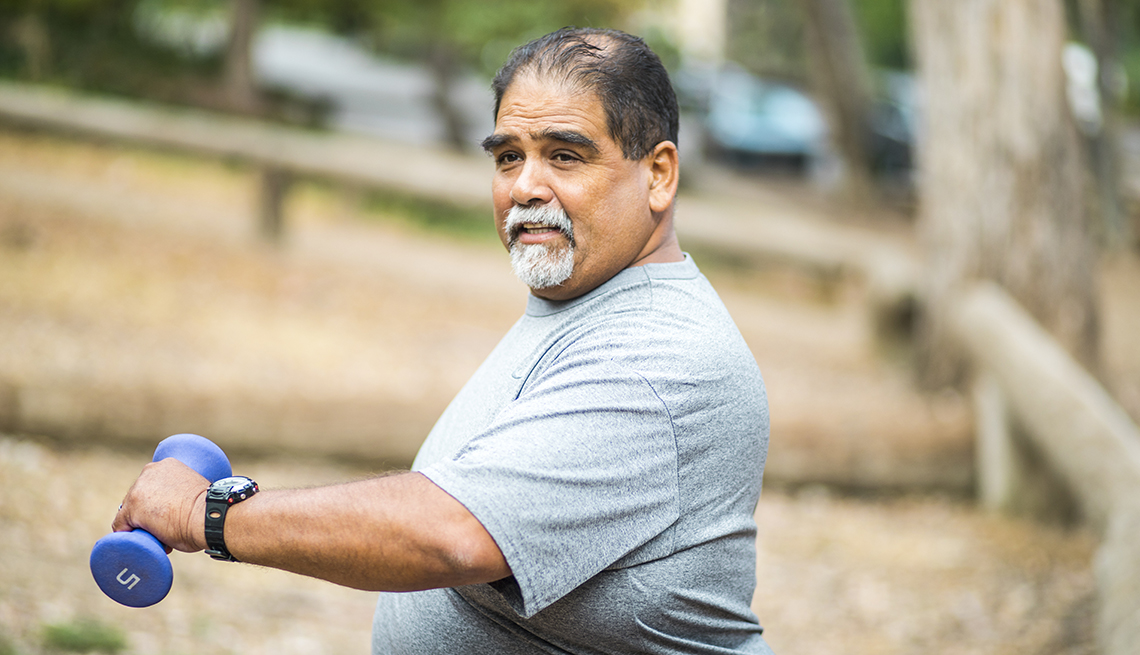 Un hombre se ejercita al aire libre sosteniendo pesas de mano.