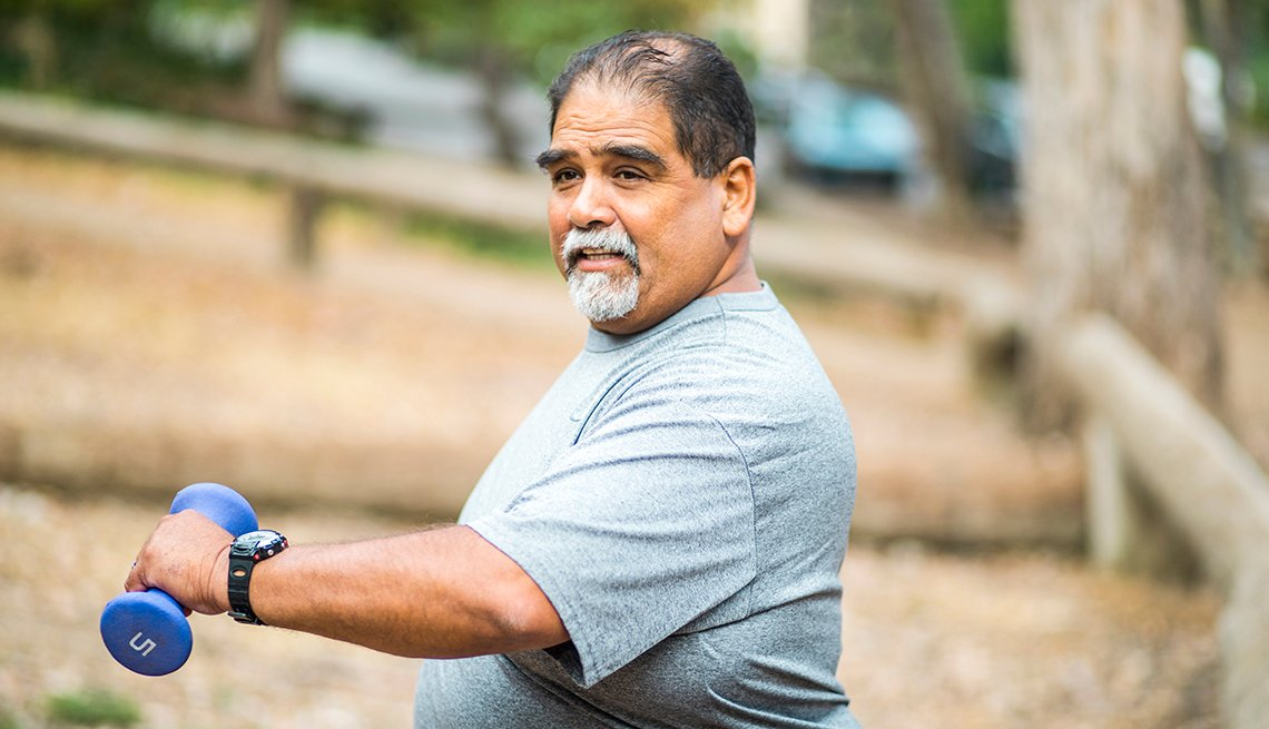 a man exercises outdoors holding hand weights
