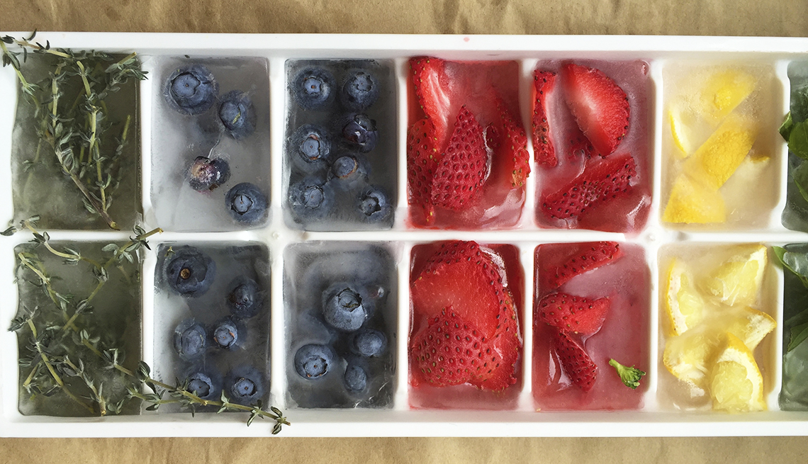 assorted fruit and herbs frozen in an ice cube tray