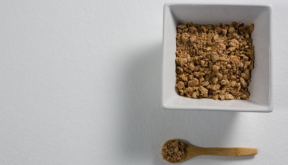 Bowl of Grape-Nuts with spoon on white background