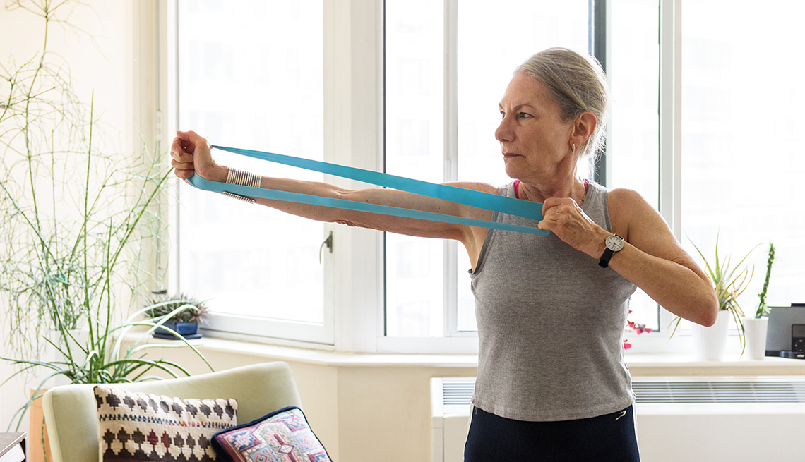 woman in her home using an exercise band