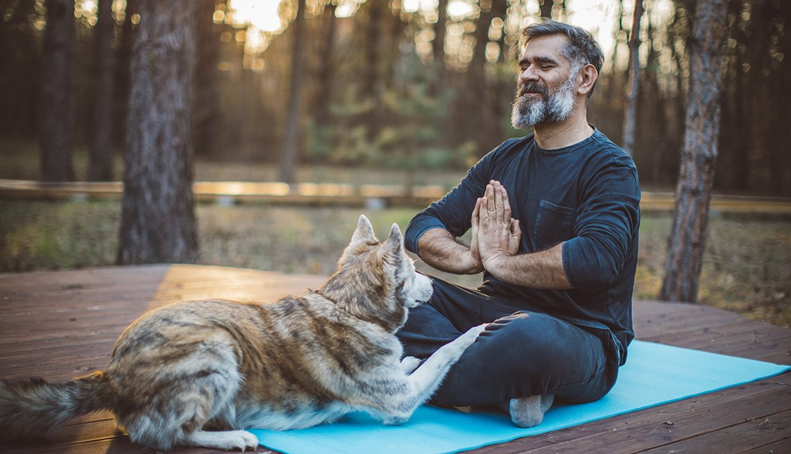 man meditating outdoors on a yoga mat with his dog next to him