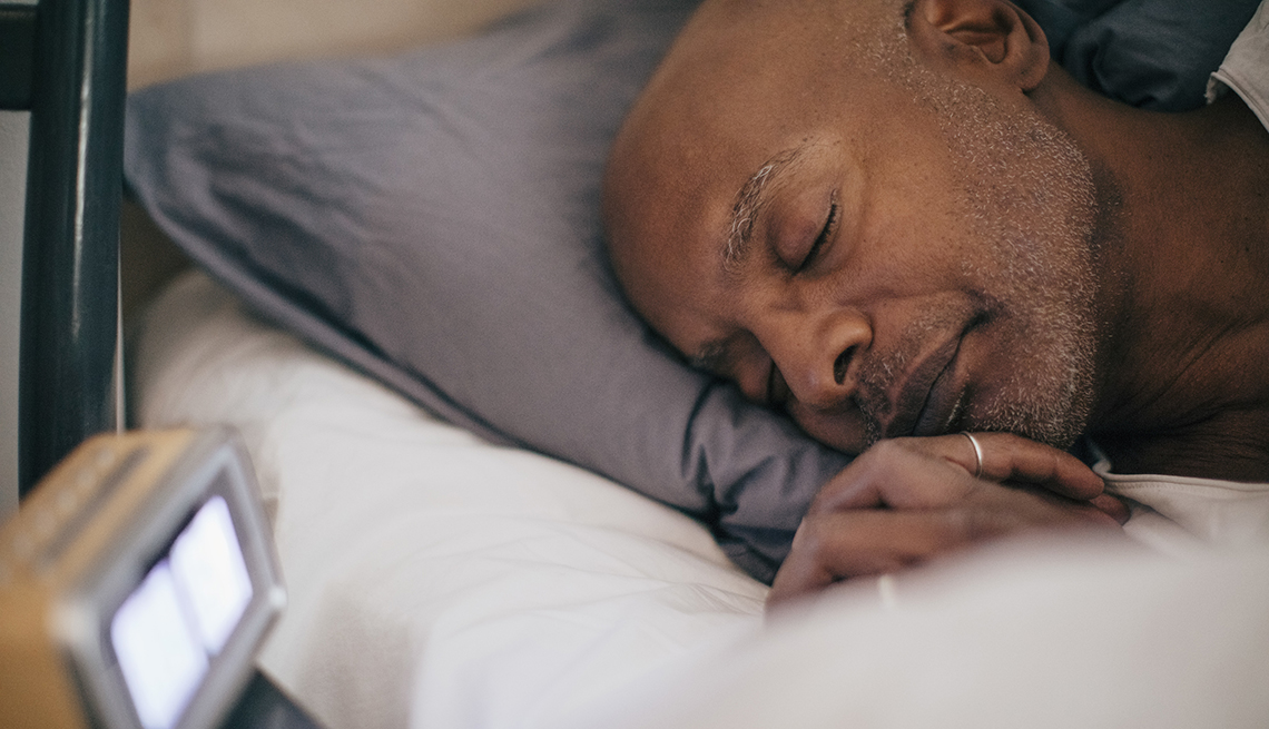 man asleep in bed showing alarm clock on bedside table