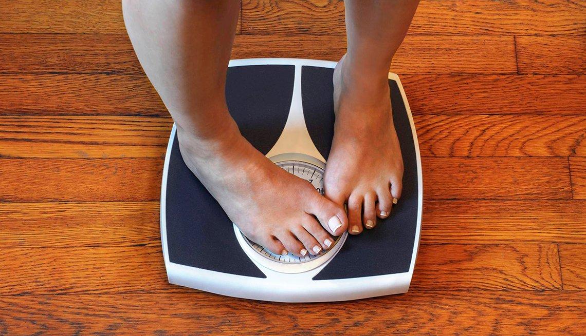 Una persona se pesa en una balanza