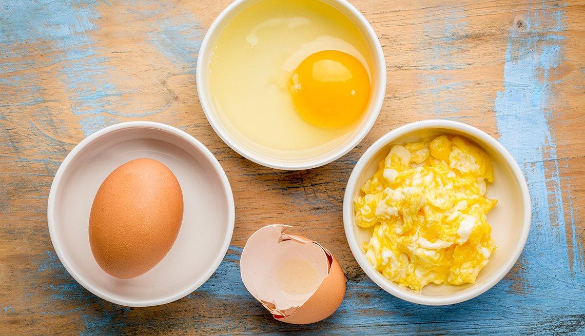 Huevos crudos y revueltos sobre una mesa de madera