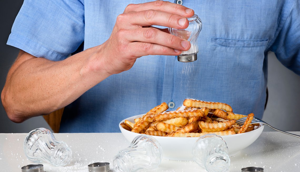 A person is pouring salt onto french fries