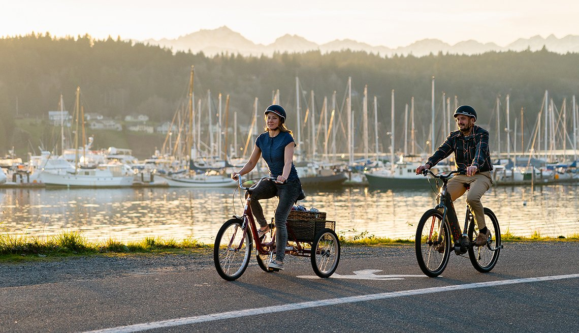 two people riding the tristar burg and vida bikes along a pretty harbor