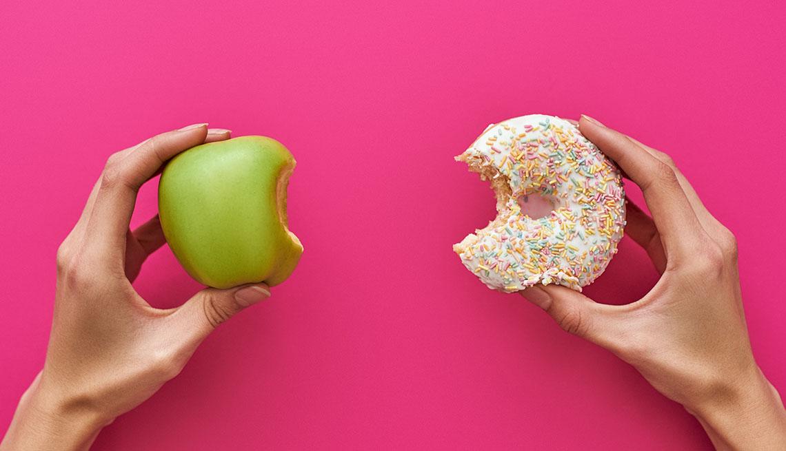 Dos manos, una sostiene una manzana y la otra una dona