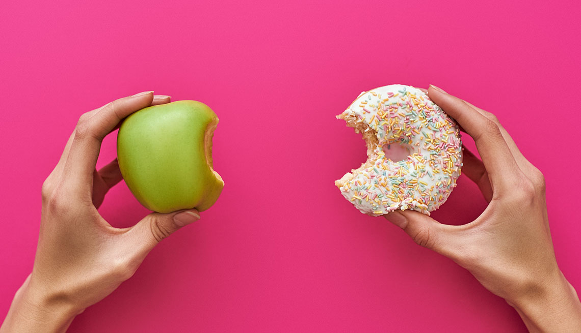 pair of hands, one holding an apple, one holding a donut
