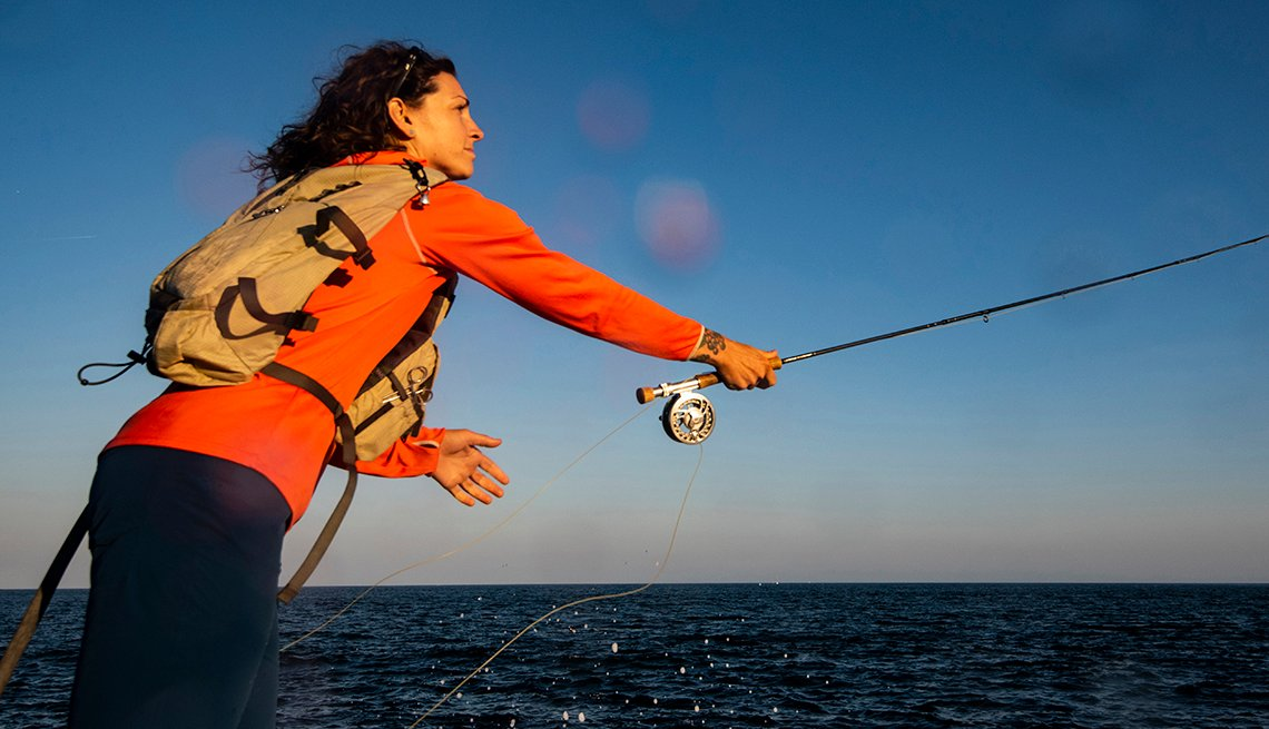 a woman casting a fishing line into the ocean in Maine