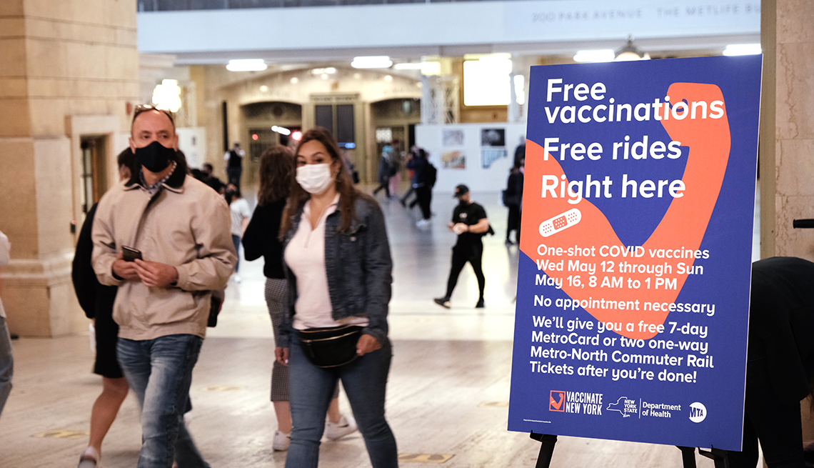 People walk through Grand Central Terminal where a pop-up site for COVID-19 vaccinations opened on May 12, 2021 in New York City. A sign reads free vaccinations - free rides.