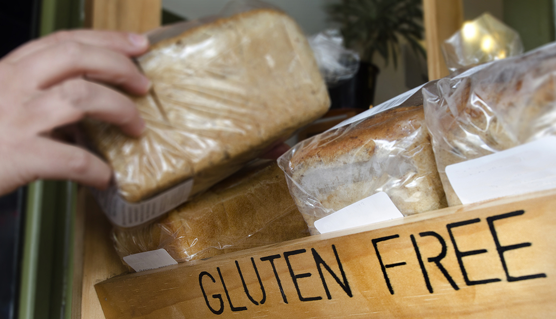 A hand picks up a gluten free loaf of bread