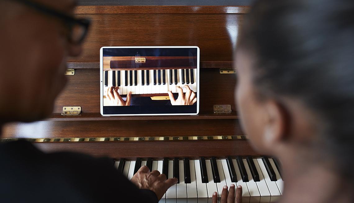 Una pareja aprende a tocar el piano