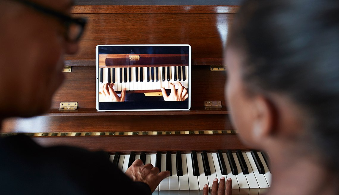 people taking a virtual piano lesson with their smart tablet