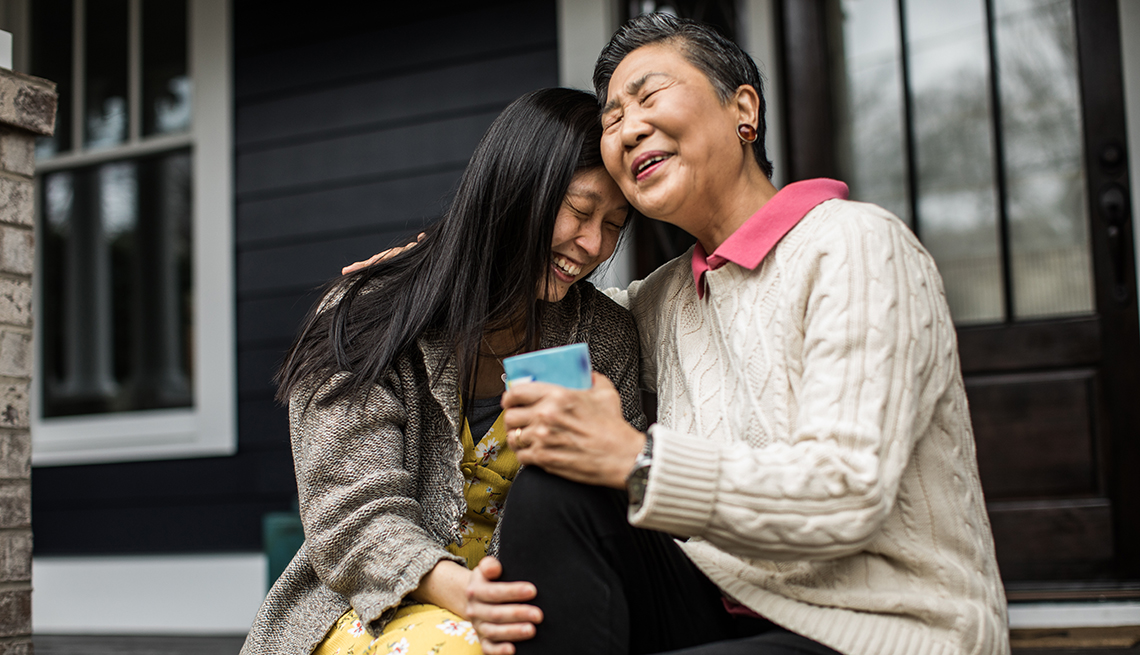 woman and her mother hugging and laughing on the porch
