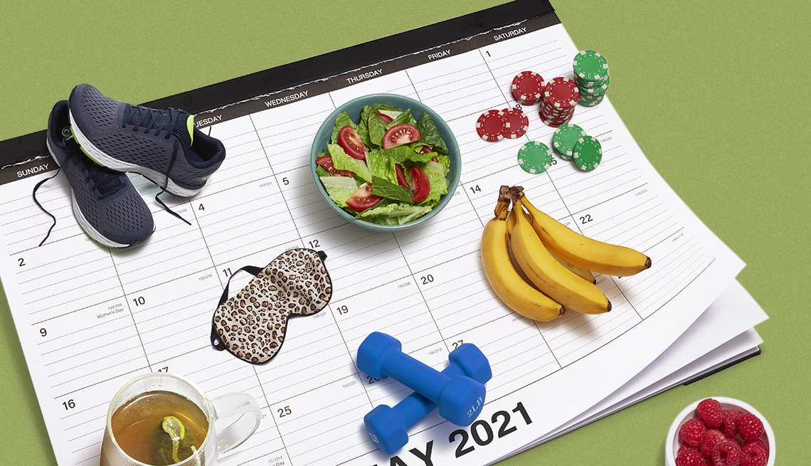 desk calendar with health related objects on top such as dumbbells sneakers a salad in a bowl a batch of bananas an eye mask for sleeping and a cup of green tea