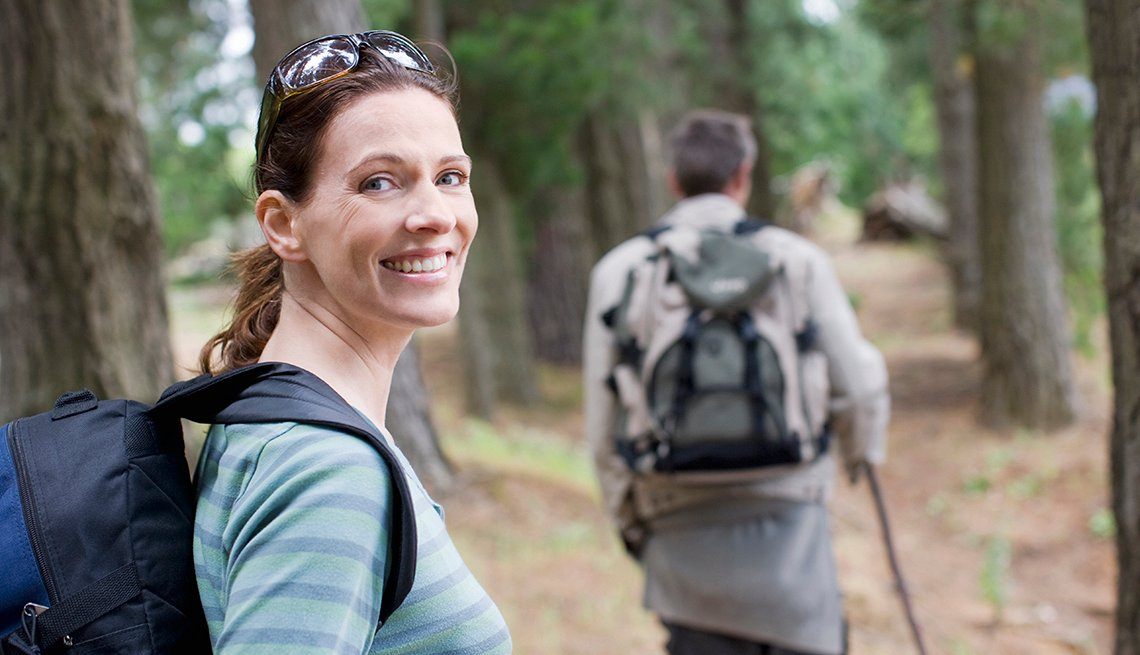 couple hiking in the woods, woman smiling at the camera