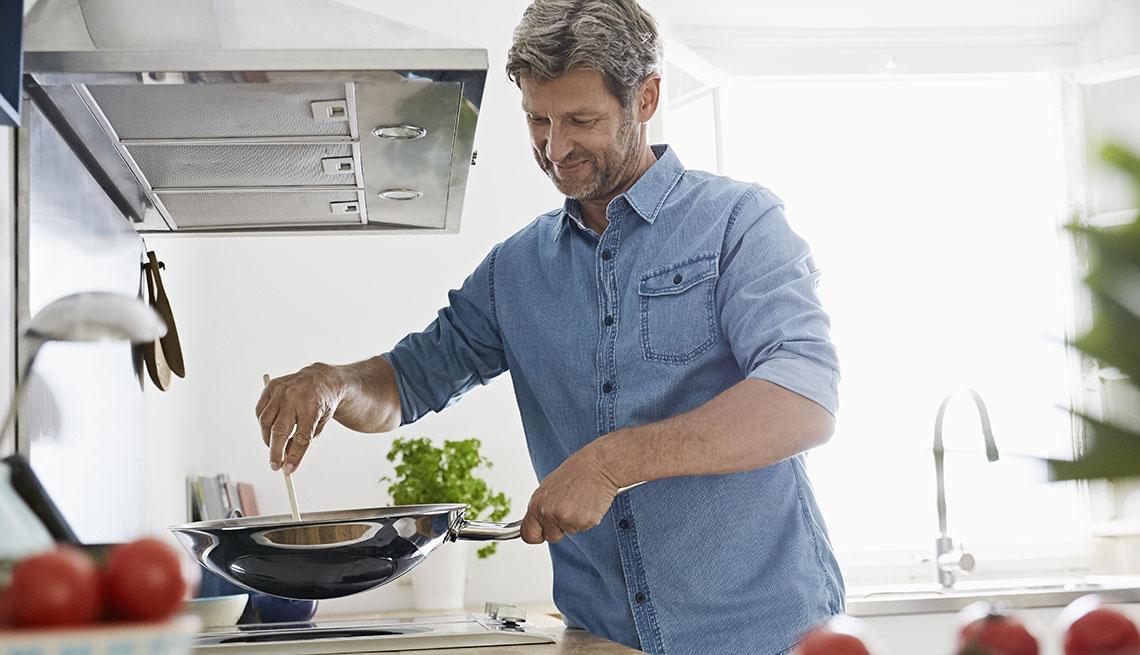 mature man cooking in bright kitchen