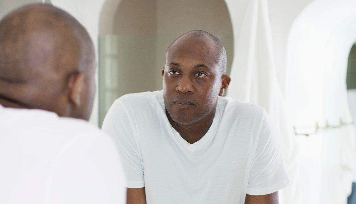Un hombre se mira al espejo