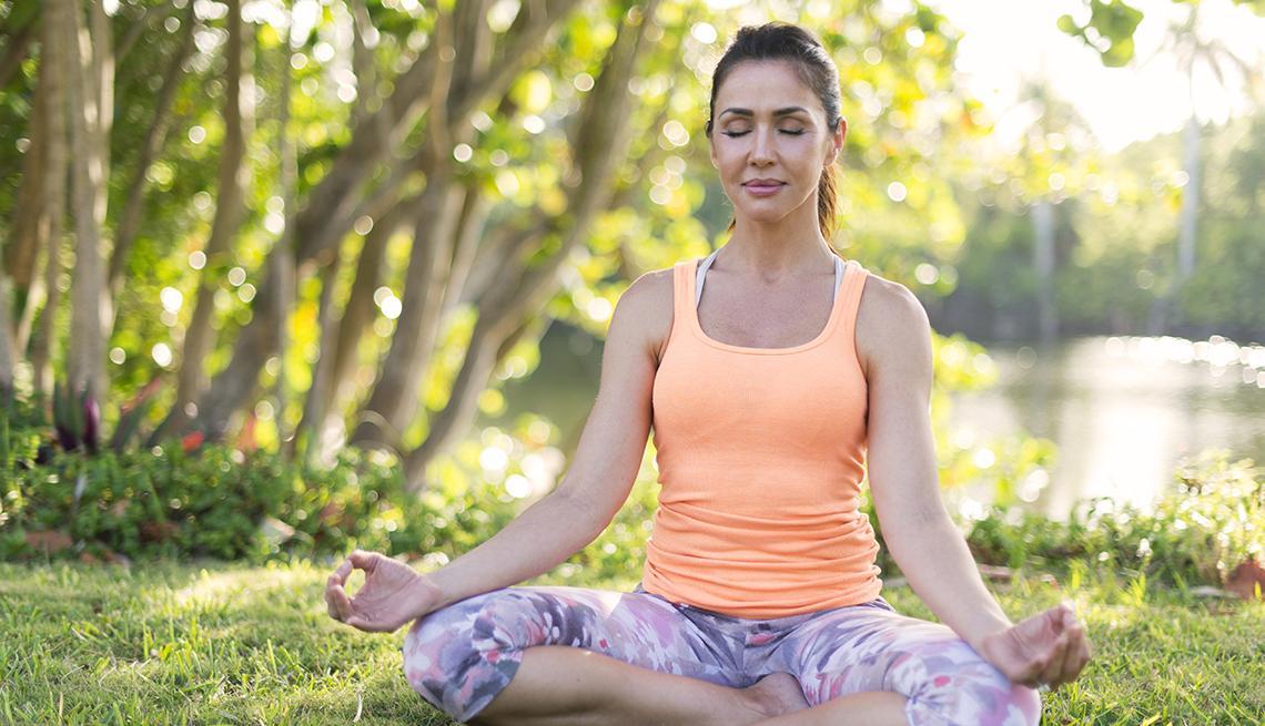 Una mujer meditando en un parque