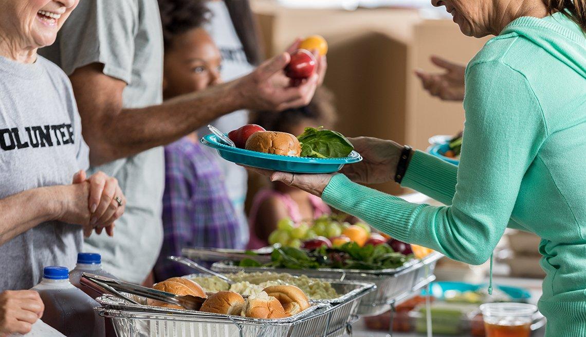 volunteers serves meals to older people in need
