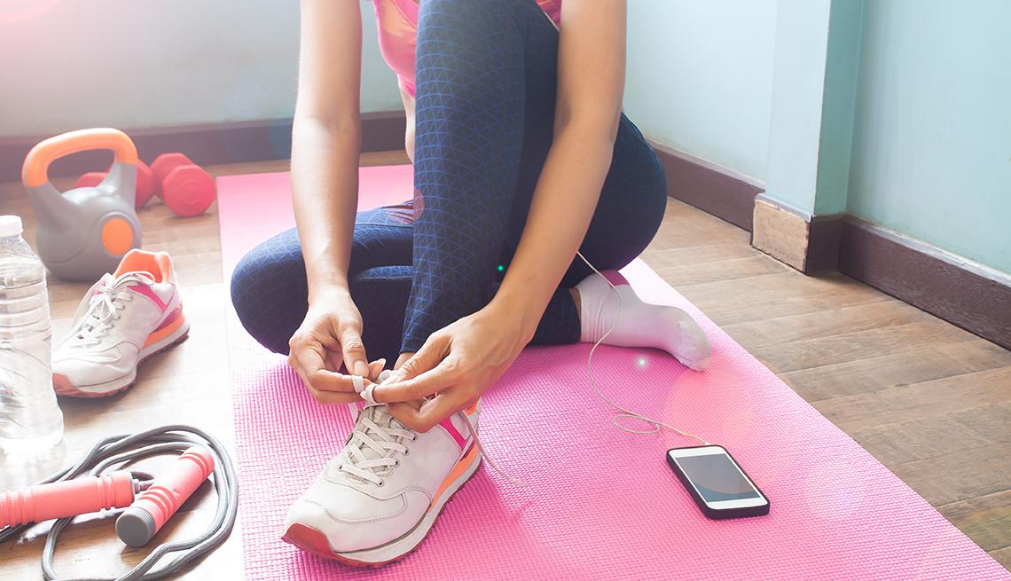 Una mujer se amarra las zapatillas de correr y cerca tiene varios aditamentos de ejercicios